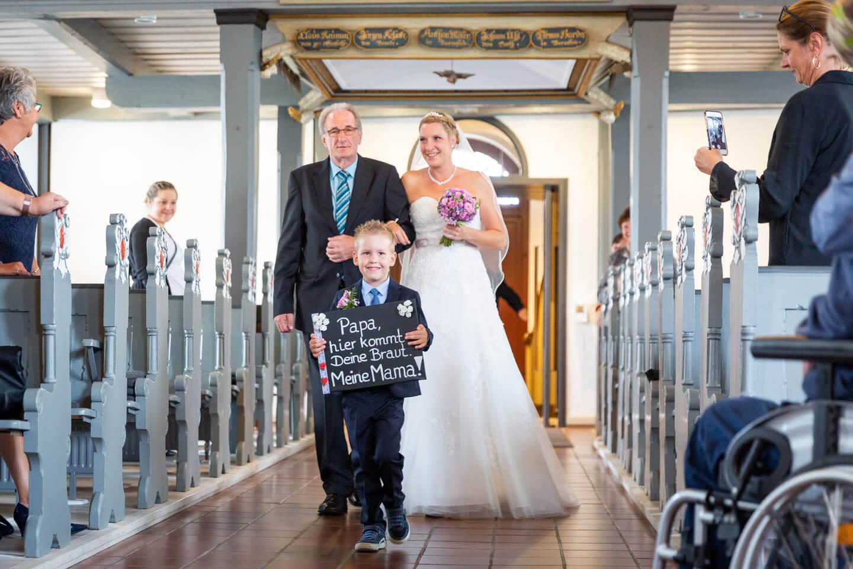 Braut wird vom Vater zum Altar geführt, Kind geht vorweg