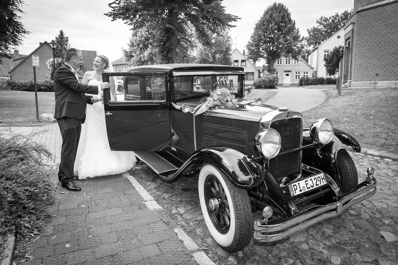 Brautpaar steigt ins historische Auto ein