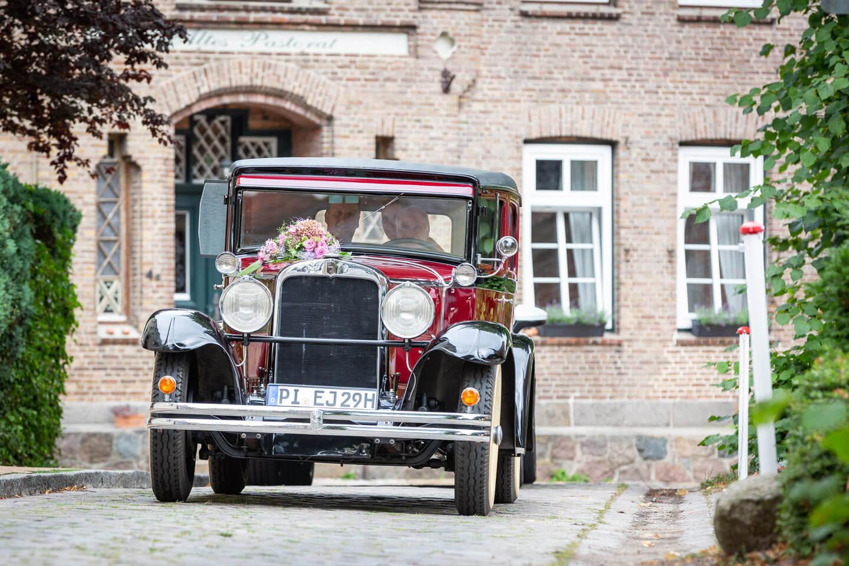 Hochzeitsauto faehrt durch kleine Gasse neben der Kirche in Barmstedt