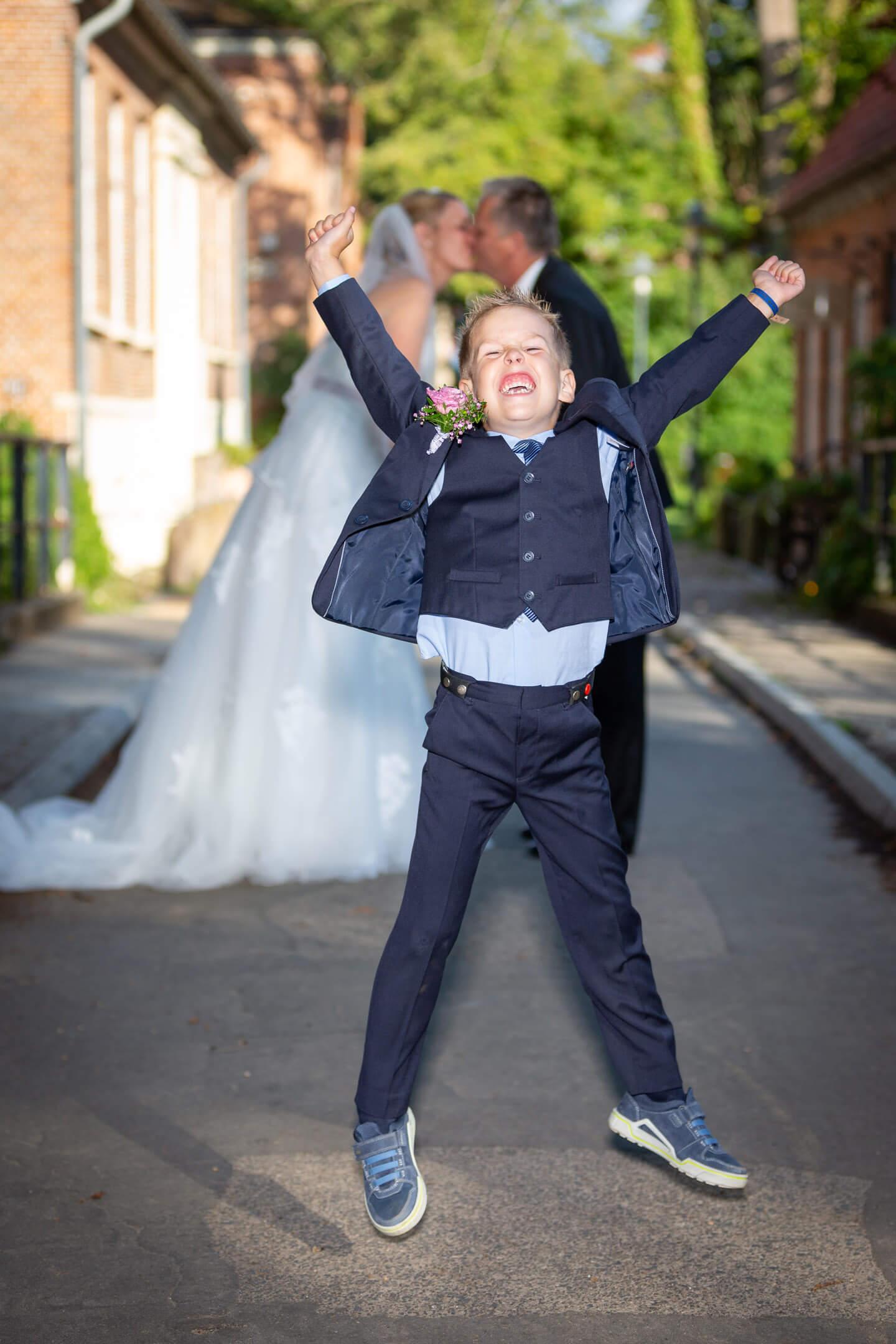 Kind springt vor Freude in die Luft, im Hintergrund küssen sich die frischverheirateten Eltern