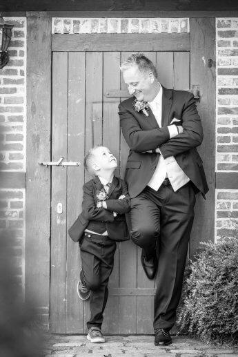 Tolles Hochzeitsfoto: Vater und Sohn lehnen sich in ihren Hochzeitsanzuegen gegen eine Wand und blicken sich an.