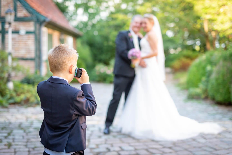 Kind fotografiert das Hochzeitspaar