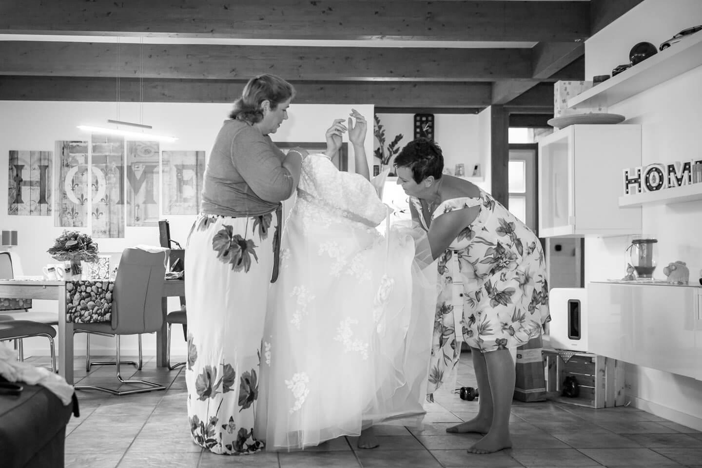 Braut schluepft bei einer Hochzeitsreportage ins Brautkleid