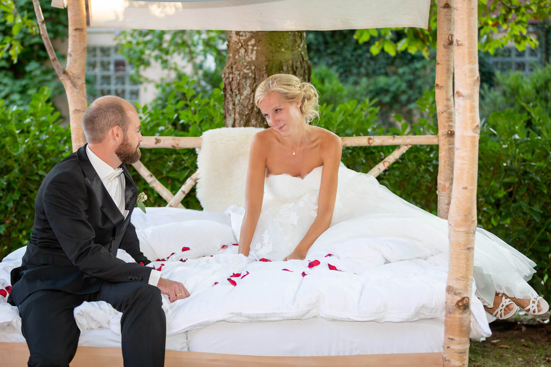 Hochzeitspaar im selbst gezimmerten Bett mit Rosenblättern