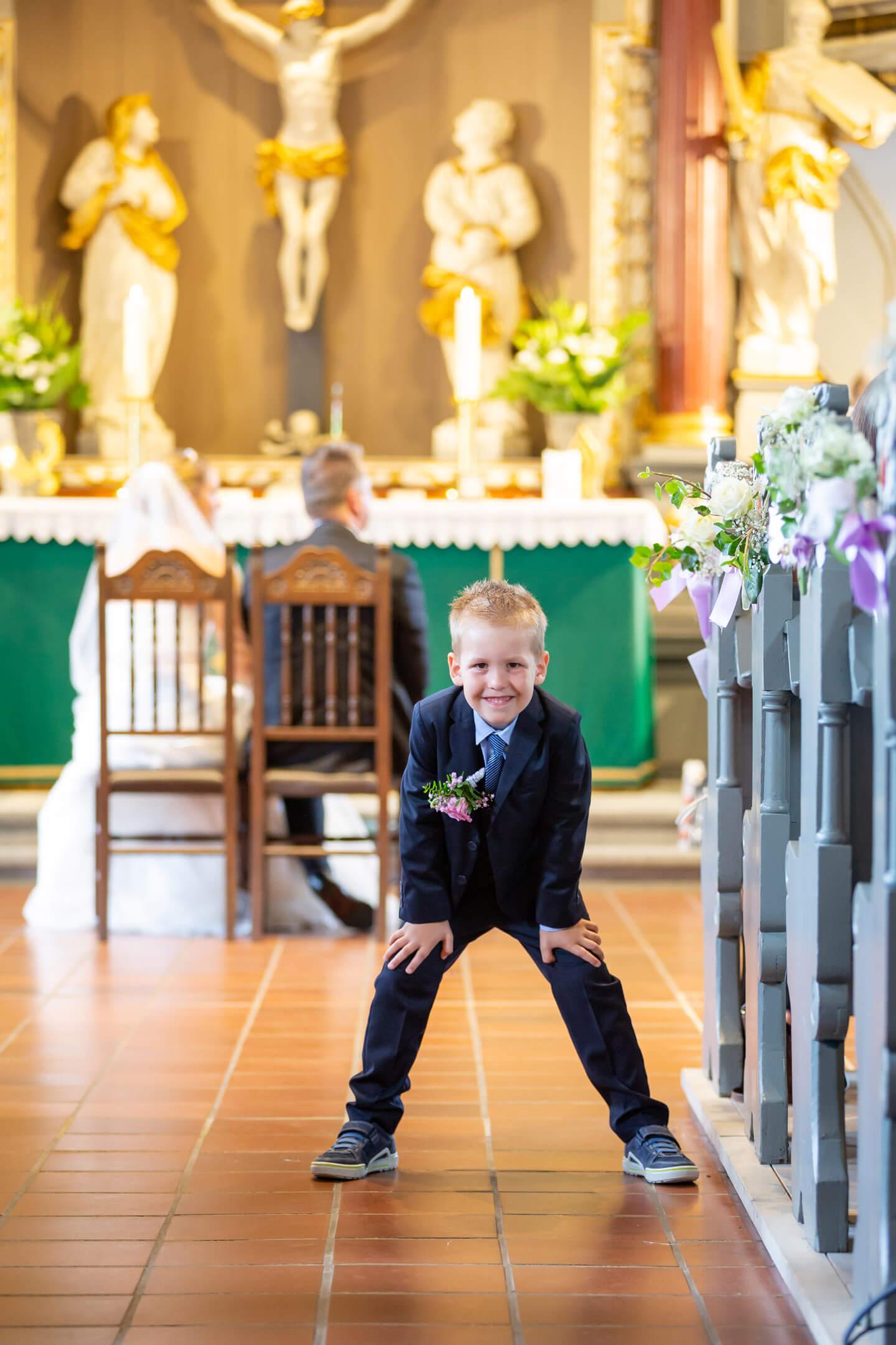 Kind guckt verschmitzt vom Kirchengang in die Kamera. Im Hintergrund sitzt das Brautpaar am Altar
