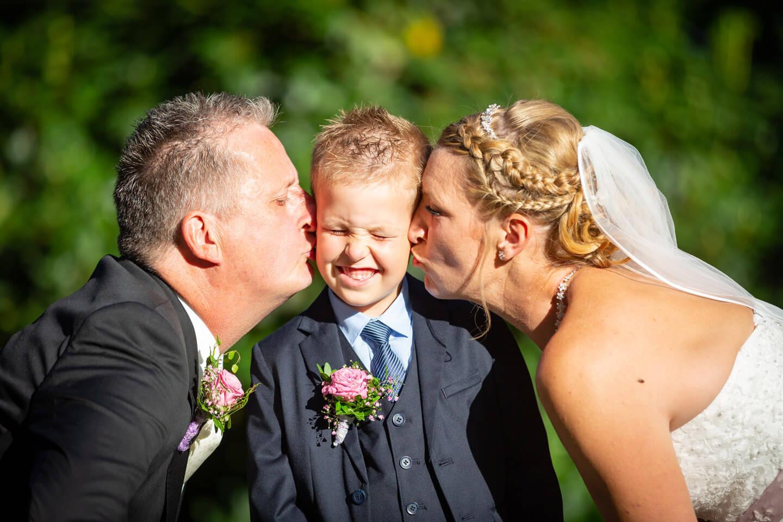 Hochzeitsfoto von Brautpaar, das von beiden Seiten dem Sohn auf die Wangen küsst