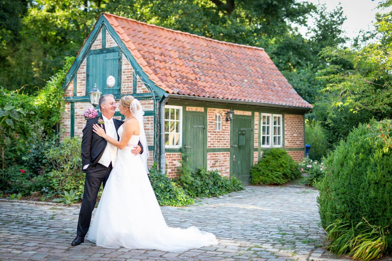Hochzeitspaar vor kleinem Fachwerkhaus