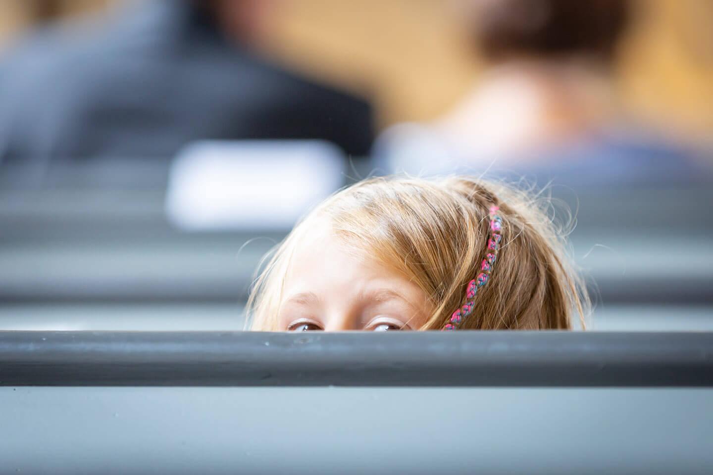 Maedchen schaut bei einer Trauung vorsichtig über die Kirchenbank in die hinteren Reihen
