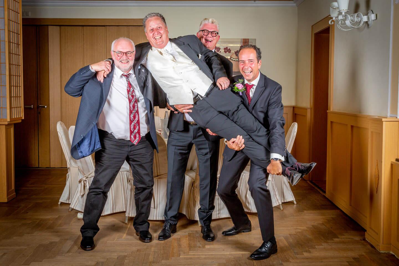 Braeutigam wird bei einer Hochzeitsreportage von seinen Jungs hochgehoben