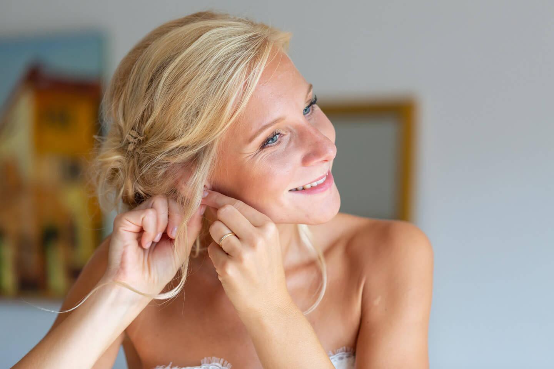 Braut steckt sich Ohrringe ein