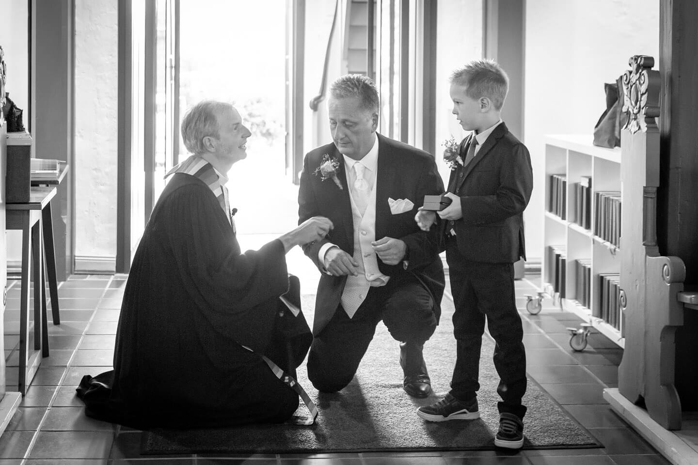 Pastor am Kircheneingang mit Braeutigam und Sohn