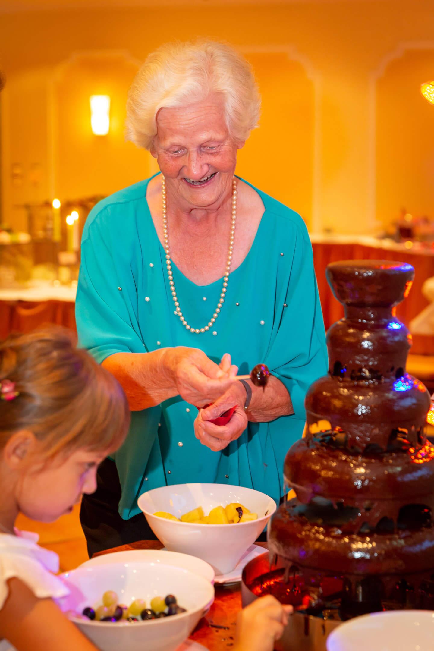 Zwei Generationen am Schokoladenbrunnen bei einer Hochzeitsfeier