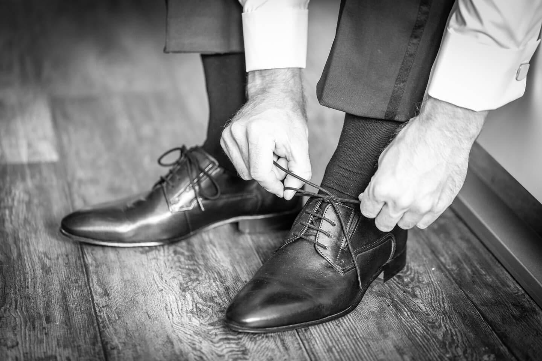 Braeutigam schnuert die Schuhe zu
