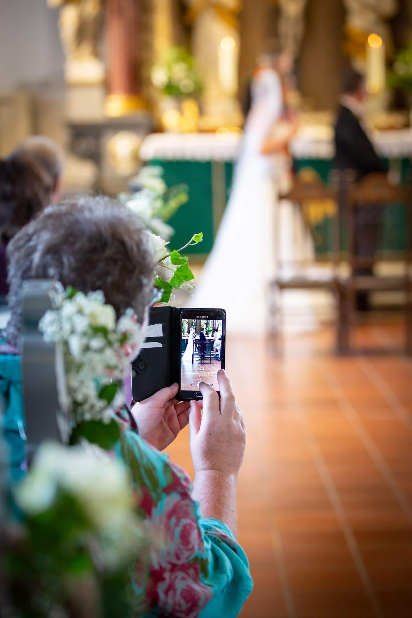 Kirchenbesucherin macht während der Trauung ein handyfoto vom Hochzeitspaar