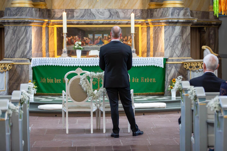 Braeutigam wartet am Altar der St.-Bartholomaeuskirche auf seine Braut