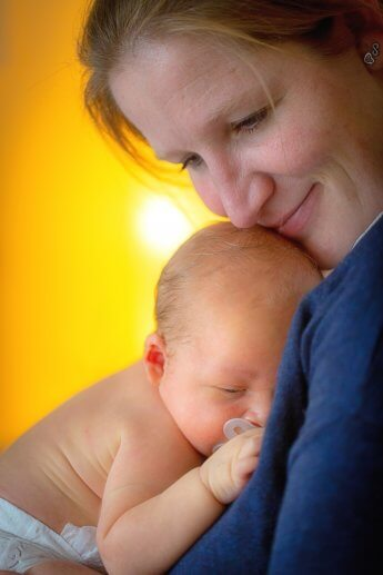 Mutter mit Neugeborenen beim Homeshooting mit dem Fotograf Florian Laeufer