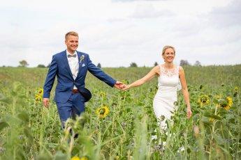 Hochzeitspaar läuft Hand in Hand durchs Sonnenblumenfeld