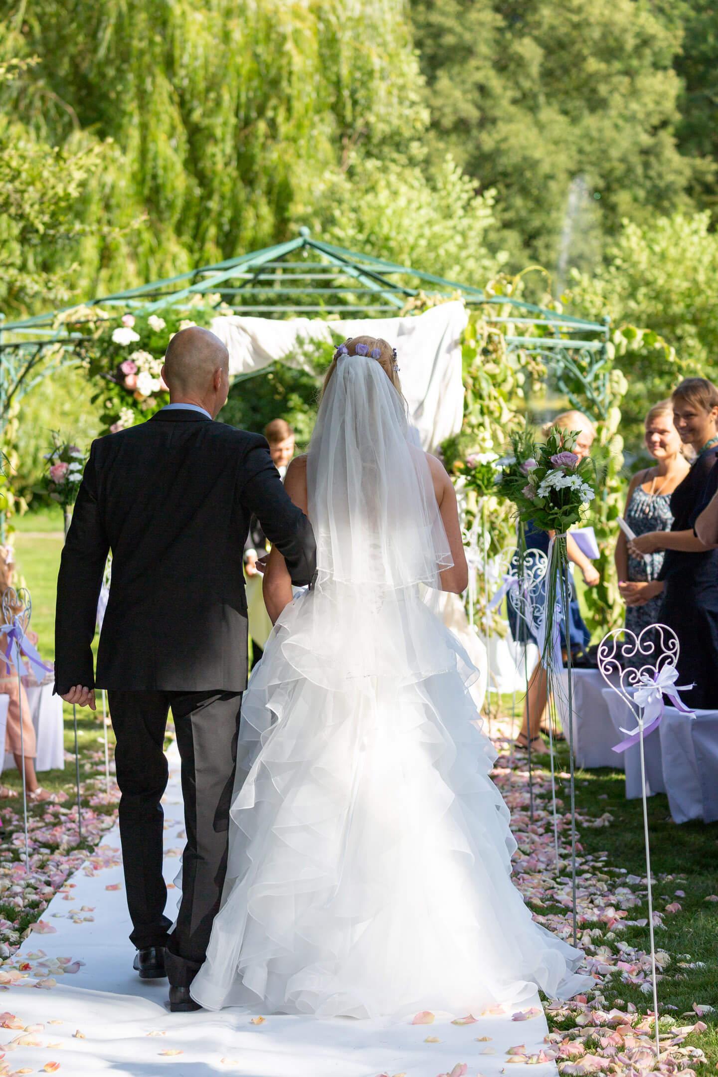 Braut wird von ihrem Papa zum Altar geführt