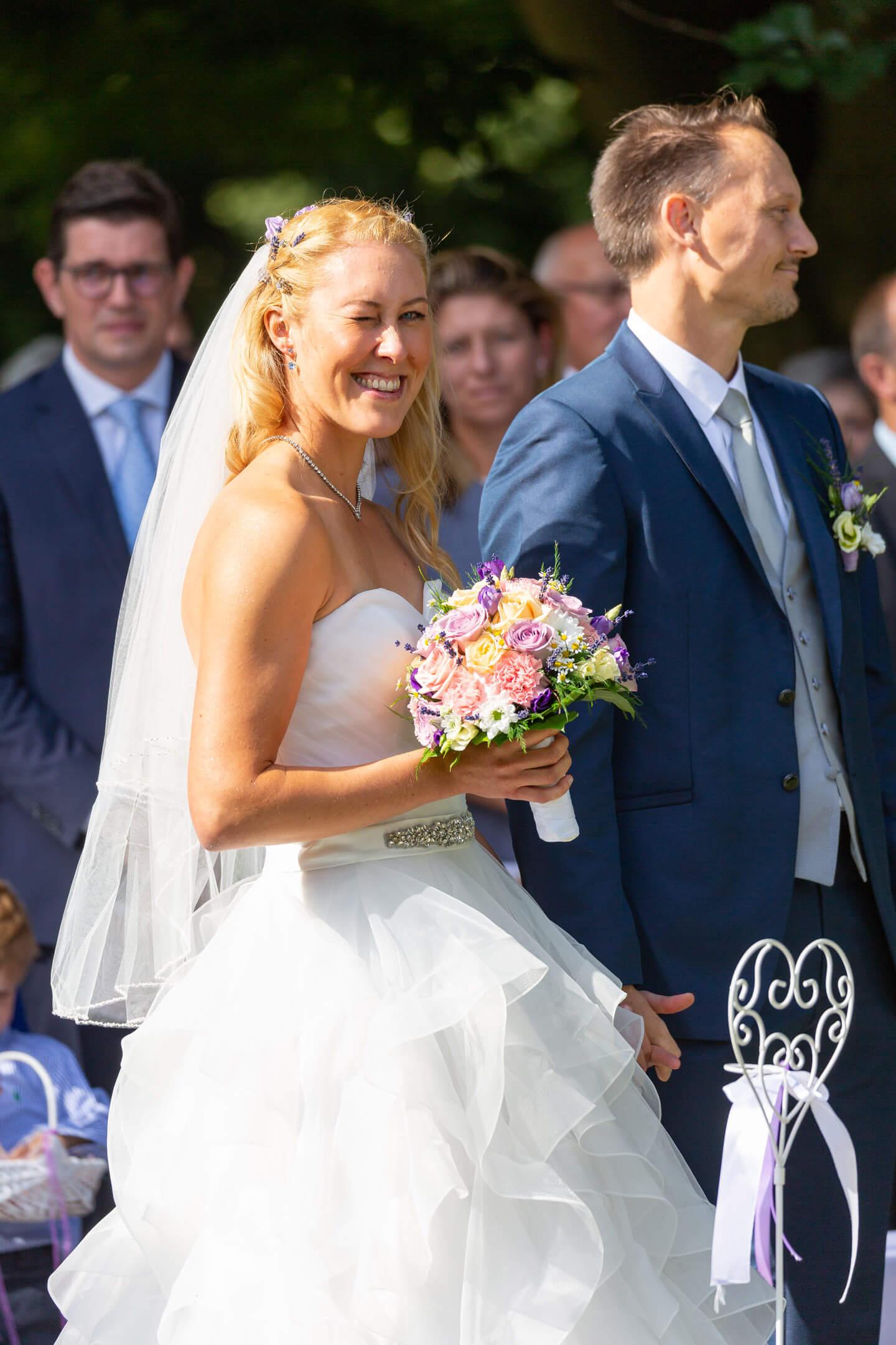 Braut zwinkert bei der freien Trauung dem Hochzeitsfotograf Florian Läufer zu