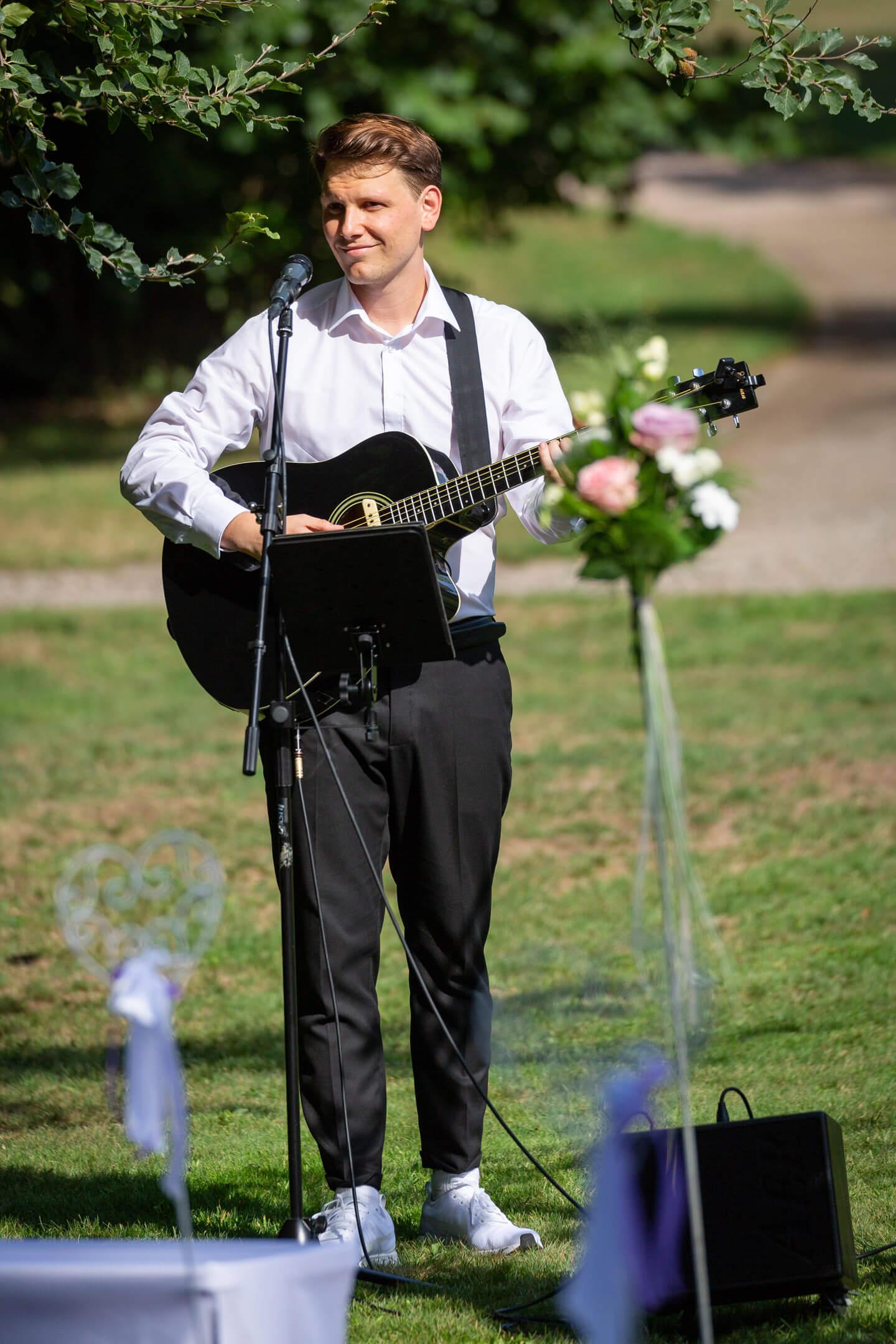 Sänger Dominik Schwarzer mit Gitarre bei einer freien Trauung im Schloss Tremsbüttel