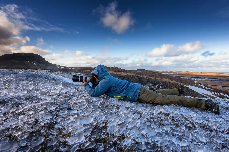 Fotograf Florian Läufer liegt bäuchlings auf einer Eisfläche für eine schöne Perspektive