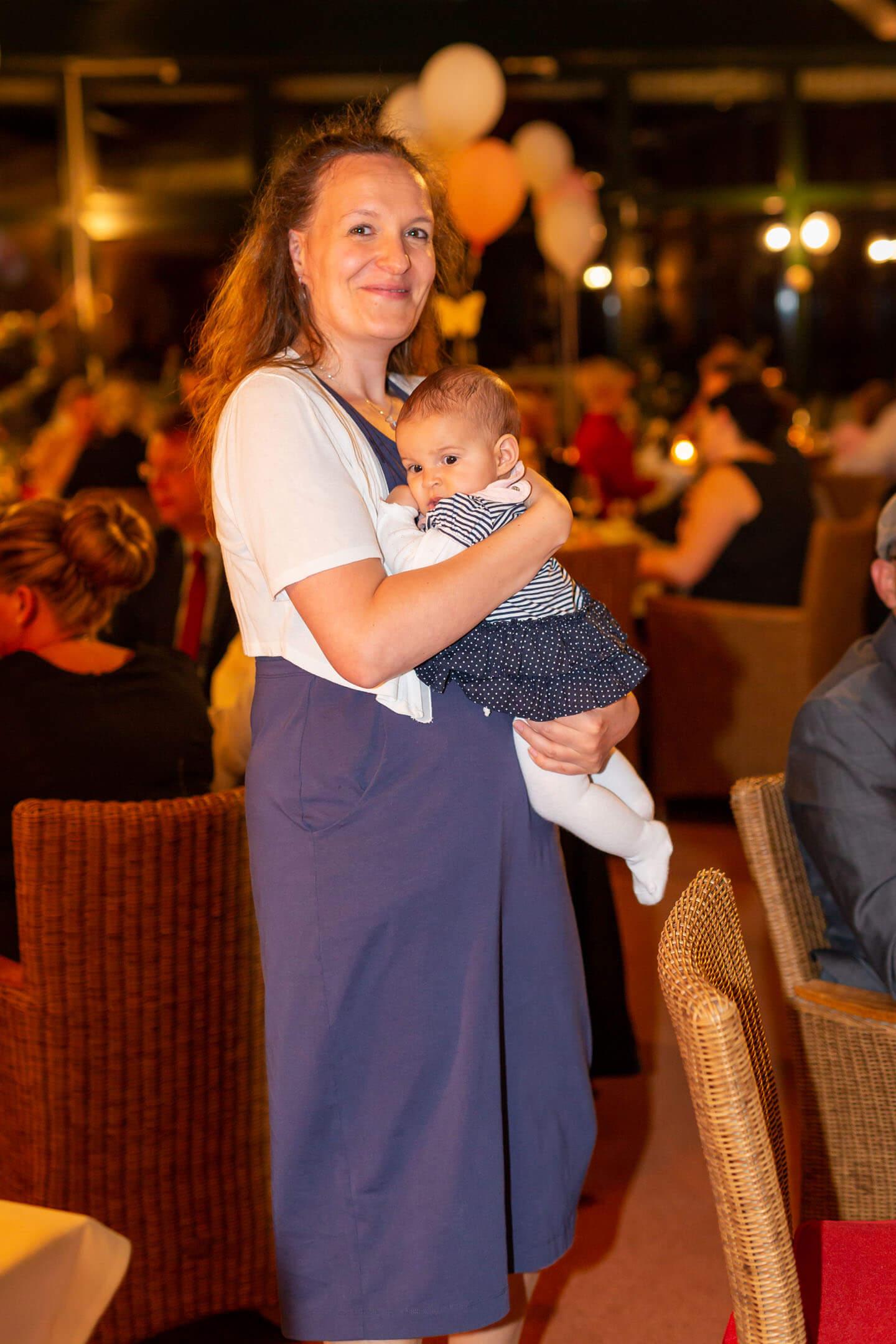 Mutter mit Neugeborenem auf Hochzeitsfeier