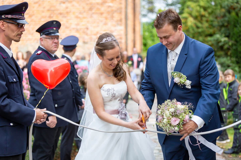 Brautpaar durchtrennt Feuerwehrschlauch