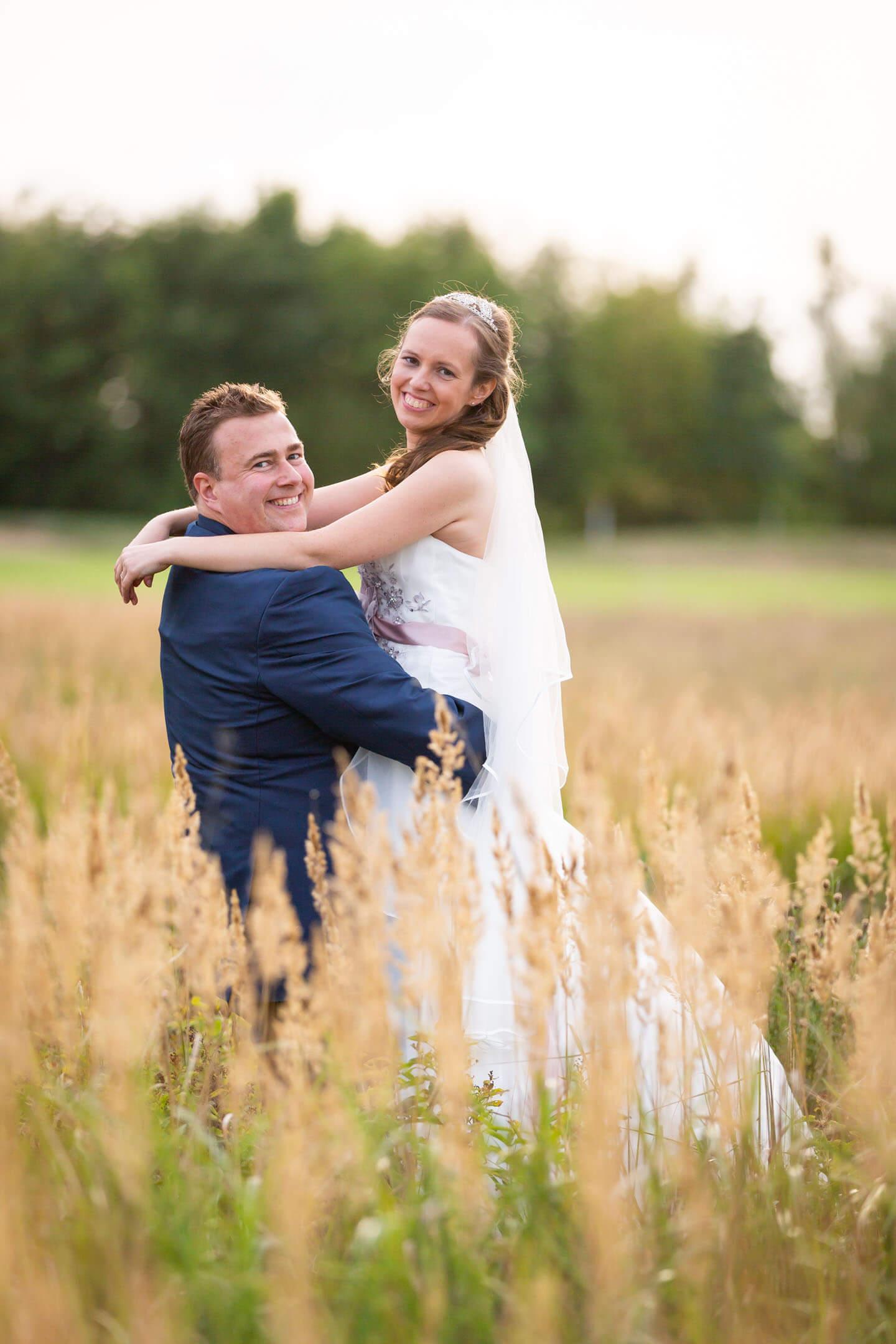 Hochzeitsshooting im Grünen. Mann hebt seine Frau hoch.