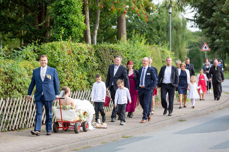 Bräutigam zieht die Braut im Bollerwagen zur Location. Hinter ihm die Hochzeitsgesellschaft