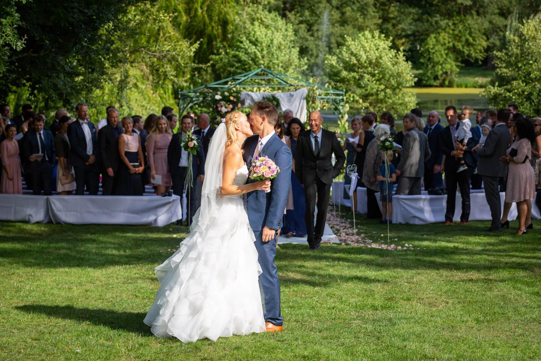 Brautpaar küsst sich nach Hochzeit im Schloss Tremsbüttel
