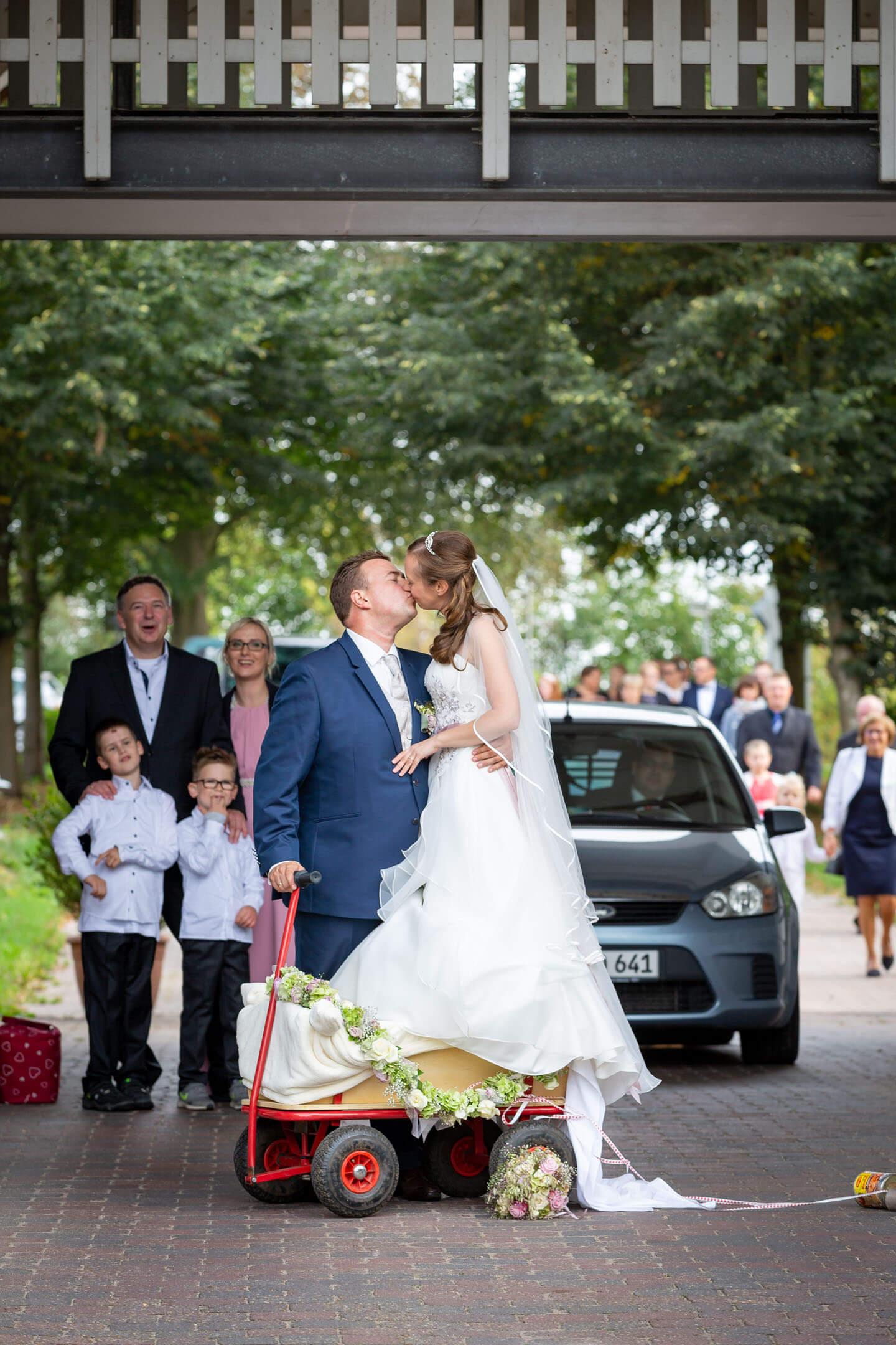 Brautpaar küsst sich, während die Braut im Bollerwagen steht