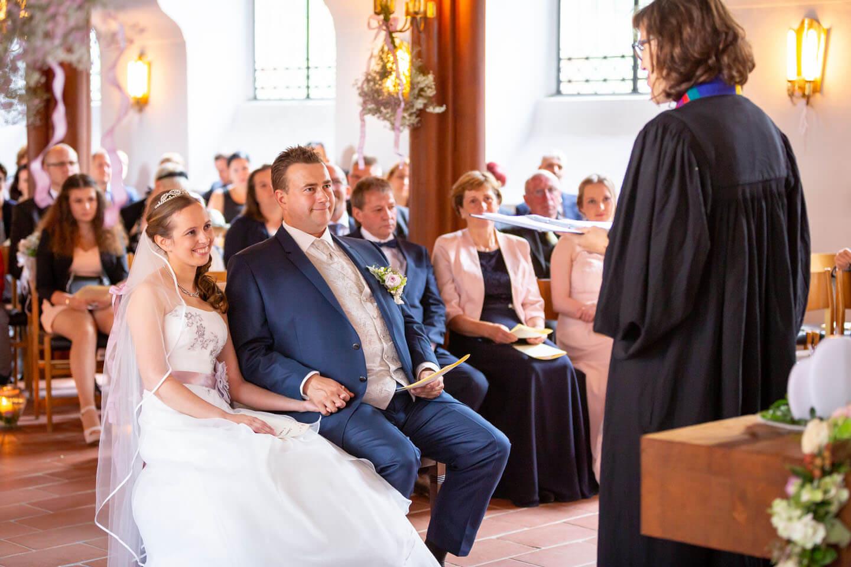 Hochzeitspaar blickt mit einem Lächeln die Pastorin in der St. Elisabeth-Kirche an