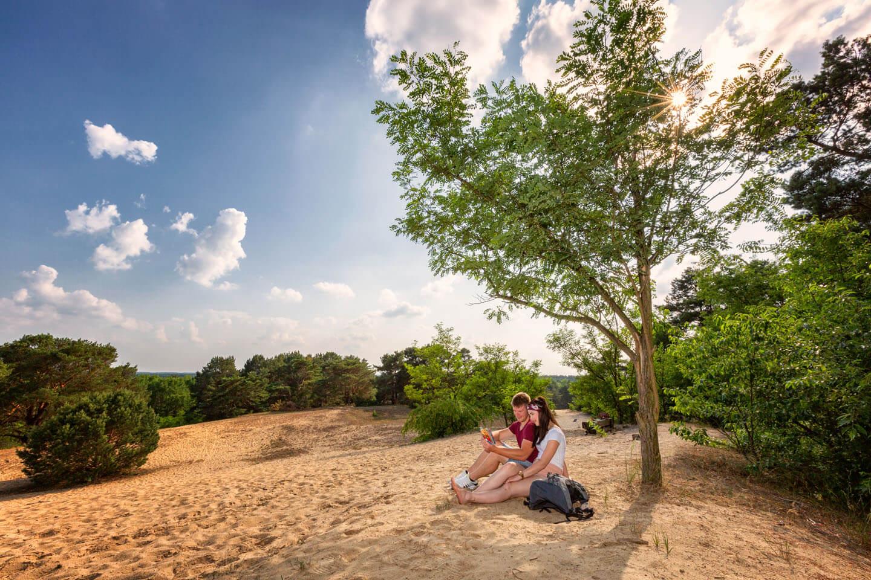 Paar sitzt auf Sandhügel in Brandenburg