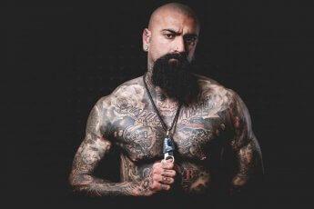 Düsteres Männerportrait eines Mannes mit Glatze und vielen Tattoos