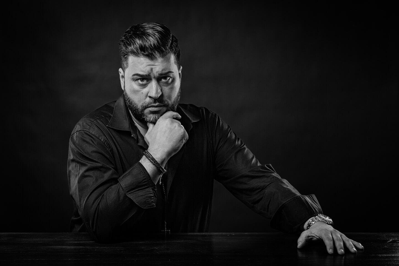 Portraitfoto Mann am Tisch in Schwarzweiss
