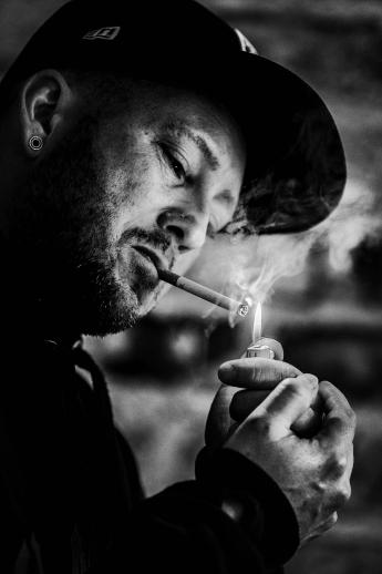 Mann zündet sich Zigarette an