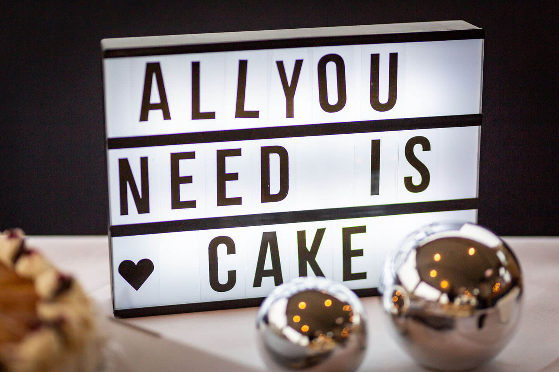 """Leuchtschild """"All you need is cake"""" auf Kuchenbüfett"""