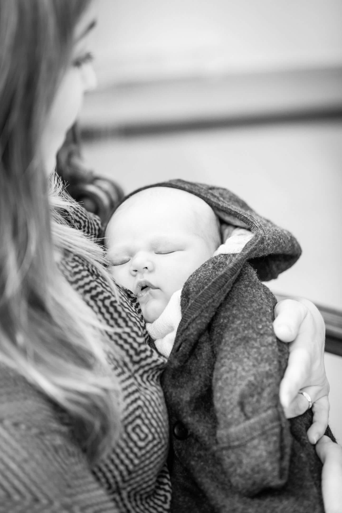Neugeborenes schlafend im Arm