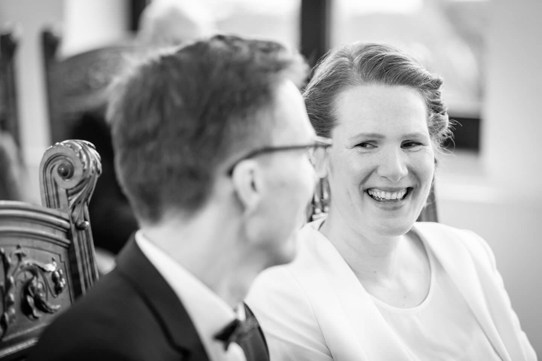 Braut lächelt Bräutigam an.