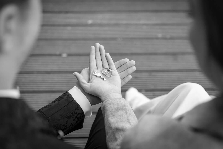 Brautpaar hält Trauringe und Schlüssel zum Liebesschloss