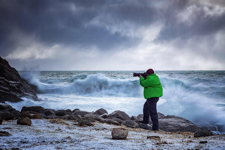 Fotograf vor brechenden Wellen auf den Lofoten