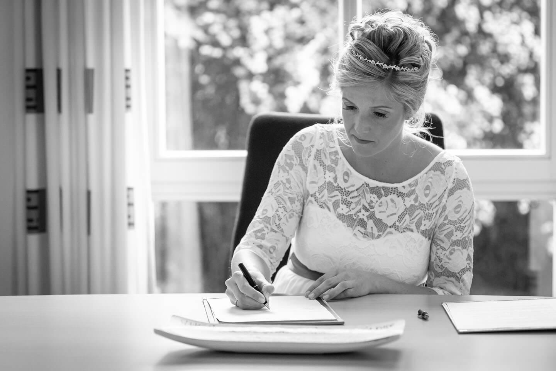 Festgehlten von dem Hochzeitsfotograf Florian Läufer aus Hamburg: Braut beim Unterschreiben der Trauurkunde