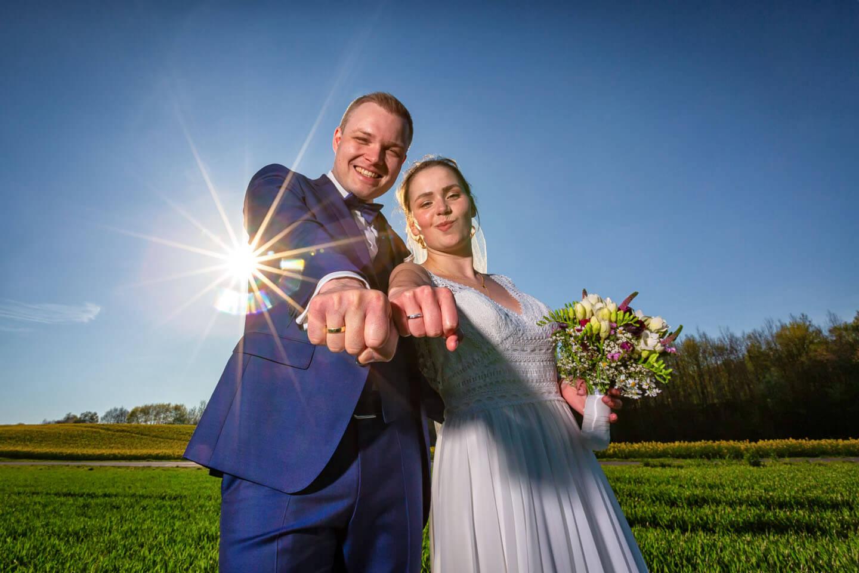 Hochzeitspaar zeigt die Eheringe