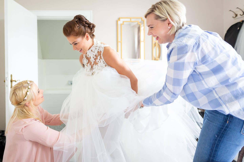 Getting Ready fotografieren. Braut, Visagistin und Trauzeugin helfen beim Brautkleid.