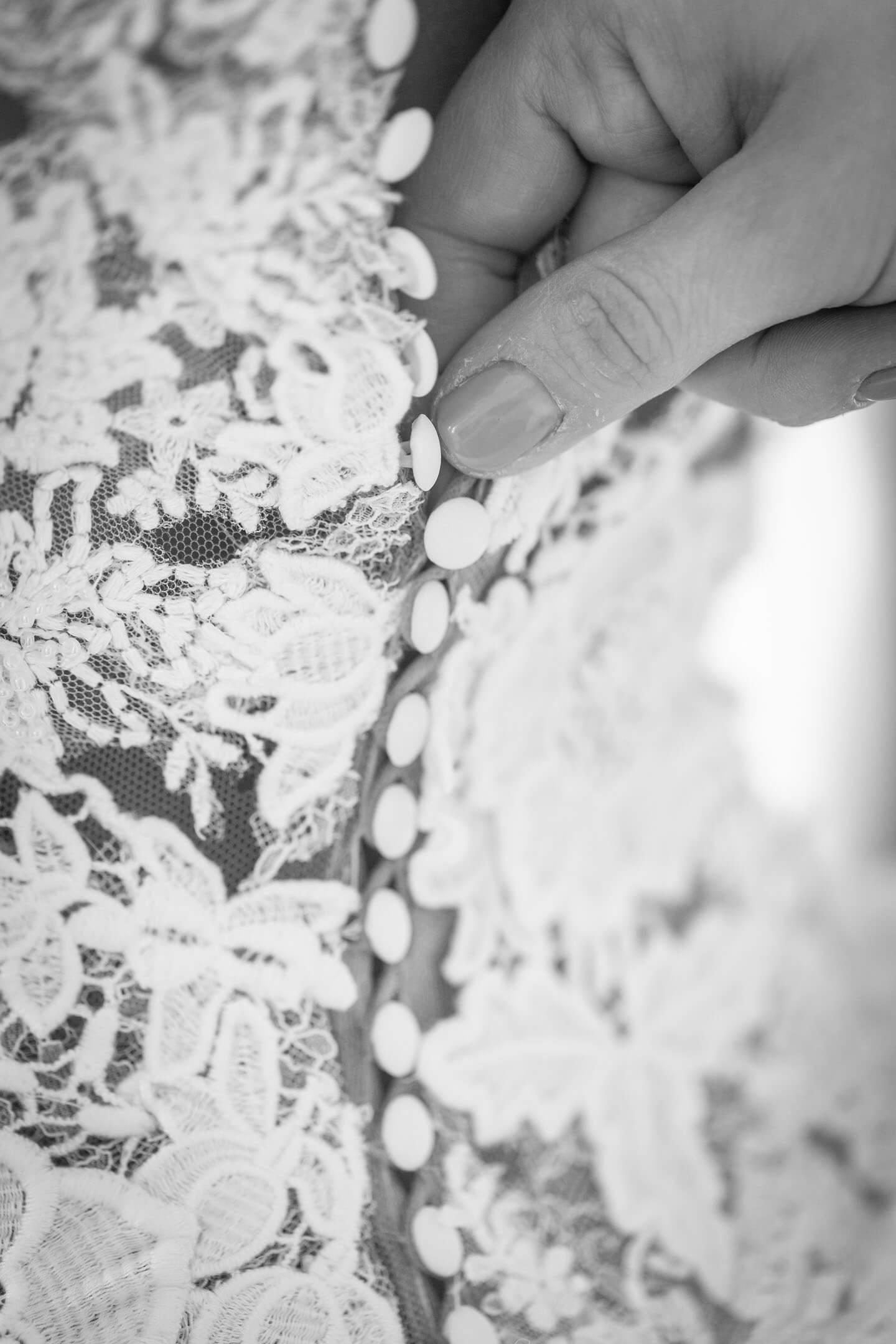 Zuknöpfen des Brautkleides beim Getting Ready.