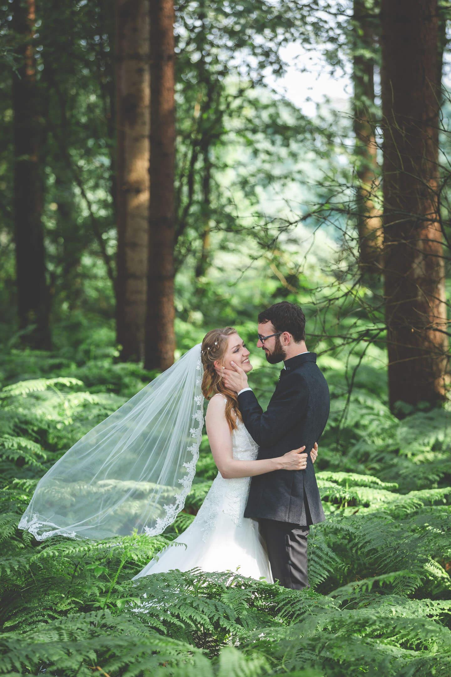 Hochzeitsfoto zwischen Farnen im Wald. Foto: Florian Läufer