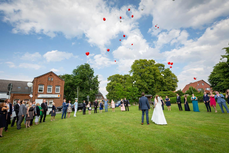Hochzeitsgäste lassen rote Ballons in den Himmel steigen.