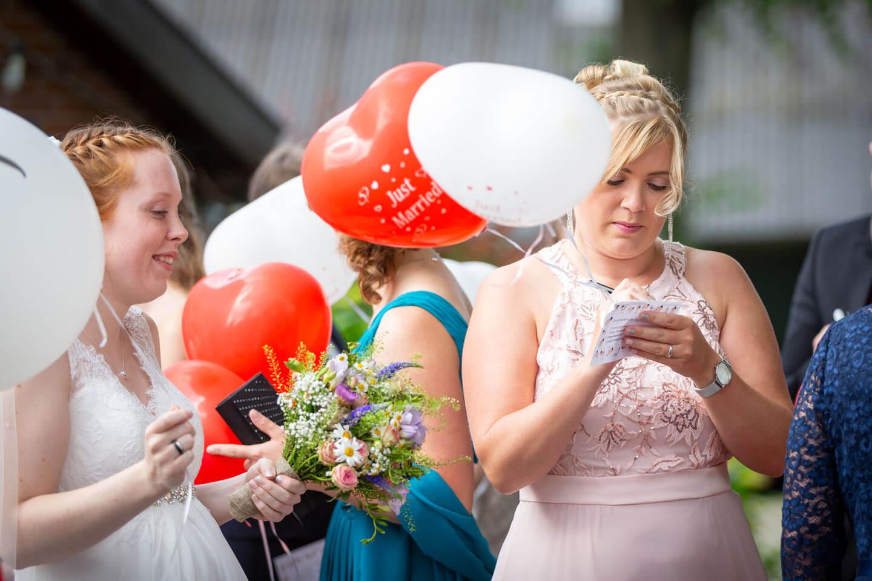 Hochzeitsgast schreibt einen Wunsch auf die Karte eines Heliumballons