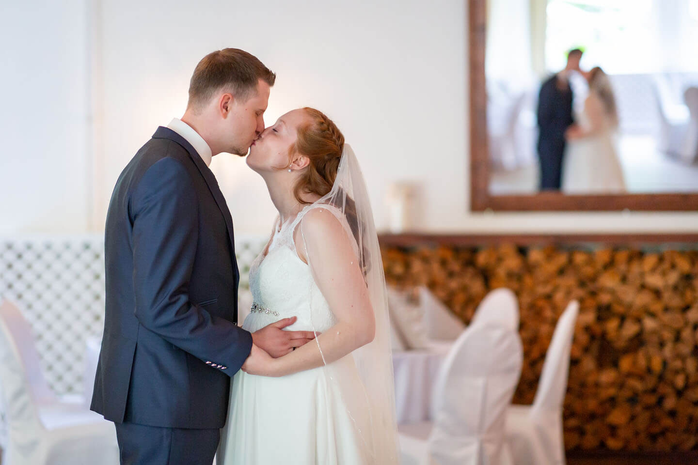 Brautpaar küsst sich und ist im Spiegel zu sehen.