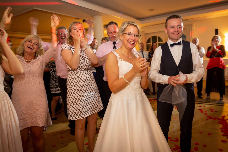 Hochzeitsgesellschaft klatscht beim hereinbringen der Hochzeitstorte